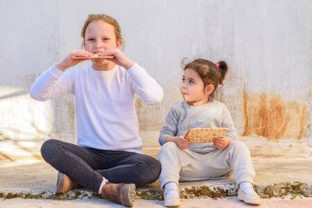 Two cute jewish girl eating matzah outdoor rural background. Stock Photo