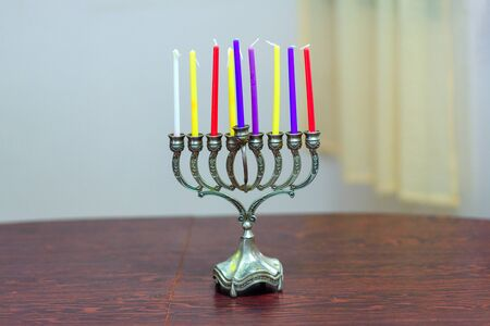 Jewish holiday Hanukkah background with menorah and colorful candles on wooden table in home. Cozy image menorah ready for lighting.
