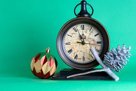 New Years clock midnight, bauble and cone on pine fir tree branch. Green background. Christmas greeting card. Stockfoto
