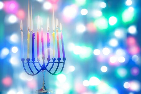 Image of jewish holiday Hanukkah on happy colorful background with menorah traditional candelabra and burning candles.