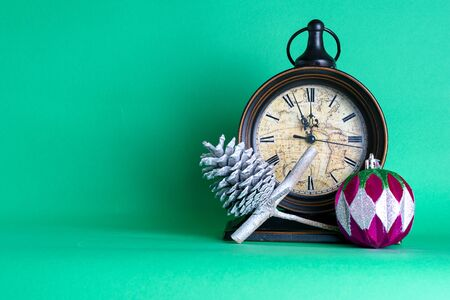 New Years clock, bauble and cone on pine fir tree branch. Green background. Christmas greeting card. Stockfoto