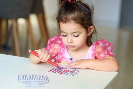 Curly brunette cute little toddler girl painting with color pen paper menorah and candle Jewish holiday Chanukah. Hebrew text : Happy Hanukkah.