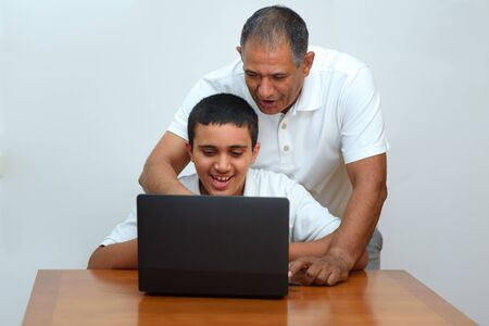 Senior Father and teenage son using laptop. Boy and dad sitting at home working with tablet computer.Happy family old grandfather and grandson on laptop.Elderly teacher trainer and teen pupil boy.