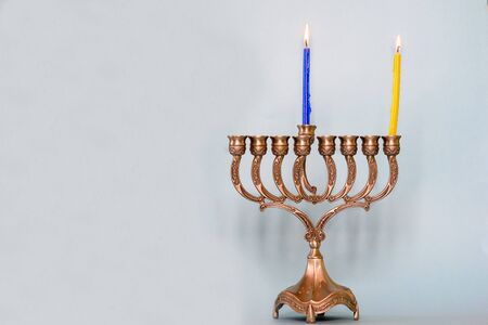 First day of Hanukkah with burning Hanukkah colorful candles in Menorah traditional Candelabra .Chanukkah-jewish holiday. Each night, another candle is added. Copy space for text.
