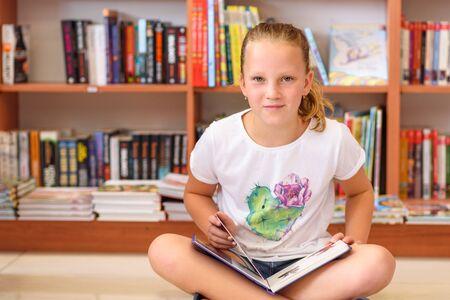 Ragazza dell'adolescente in biblioteca davanti ai libri. Bambino in giovane età sveglio che si siede sul pavimento e che legge libro. Il ragazzino legge in una libreria, circondato da libri colorati. Biblioteca, negozio, scaffalature in casa. Archivio Fotografico