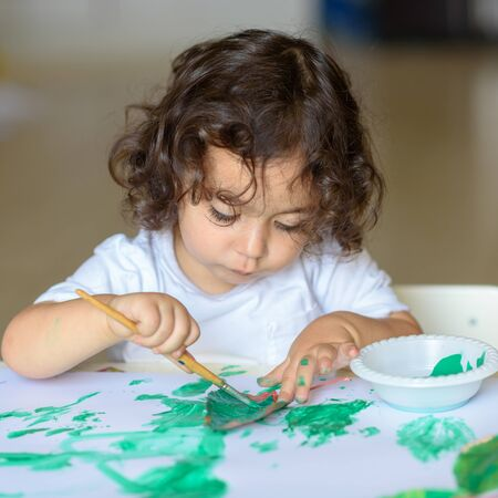 Summer, Dont Go. Portrait cute little kid drawing with green paint on fall leaf. Curly adorable child painting at table. Reklamní fotografie