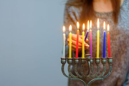 Jewish Woman lighting Hanukkah Candles in a menorah. People celebrate Chanukah by lighting candles on a menorah, also called a Hanukiyah. Each night, one more candle is lit. 版權商用圖片 - 131473986