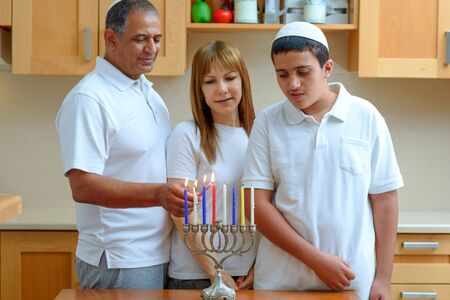 Happy multiracial jewish family is lighting candles for the Jewish holiday Hanukkah. Jewish Dad, Mom and teenager son or grandparents with grandson lighting Chanukkah Candles in a menorah for holidays Zdjęcie Seryjne
