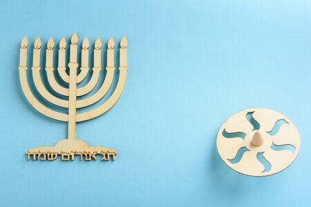 Childrens craft -Wood menorah and wooden dreidels spinning top symbols Jewish holiday Hanukkah on blue background. Written in Hebrew happy Hanukah.