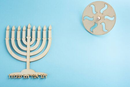 Childrens craft -Wood menorah candelabrum and wooden dreidels spinning top symbols Jewish holiday Hanukkah on blue background. Written in Hebrew happy Hanukah, cheerful holiday of light.
