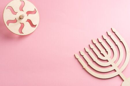 Childrens craft Wood menorah candelabrum and wooden dreidels spinning top symbols Jewish holiday Hanukkah on pink background.Top view.Copy space for your text. Archivio Fotografico
