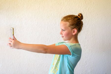 Portrait Of Stylish Girl In Neo Mint Color T-shirt Using Smartphone. Child Teenager Makes Vertical video Or Takes Photo For Story.