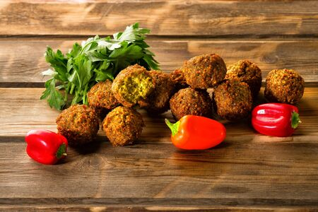 Falafel balls,sweet red mini pepper and green fresh parsley on a wooden background.Falafel plays an iconic role in Israeli cuisine and is widely considered to be the national dish of the country.