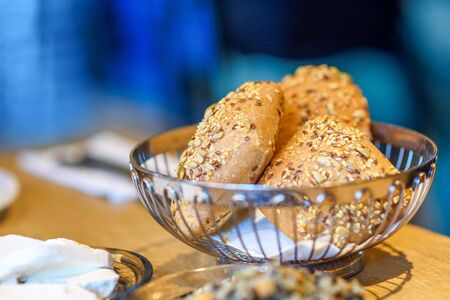 Bread rolls with cereals on wood table. Fresh pastry in buffet or resraurant.