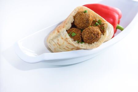 Falafel balls in a pita on a white dish and red sweet pepper background. Falafel is a traditional Middle Eastern food.