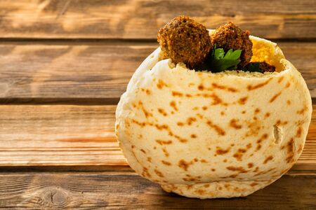 Falafel balls in a pita on a wooden background. Falafel is a traditional Middle Eastern food,commonly served in a pita great source of fiber, protein, copper, folate and other nutrients. Copy space.