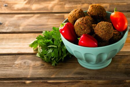 Falafel balls in a bowl and fresh vegetables on a wooden background.Falafel plays an iconic role in Israeli cuisine and is widely considered to be the national dish of the country.