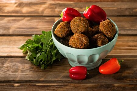 Falafel balls in a bowl and fresh vegetables on a wooden background.Falafel is a traditional Middle Eastern food, commonly served in a pita.