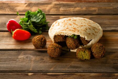 Falafel balls, pita-arabian bread and fresh vegetables on a wooden background.Falafel plays an iconic role in Israeli cuisine and is widely considered to be the national dish of the country.
