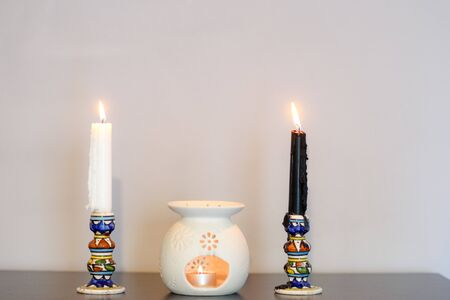 Cozy home interior decor, burning candles. White and black candles. Three burning candles on wooden table against white wall.