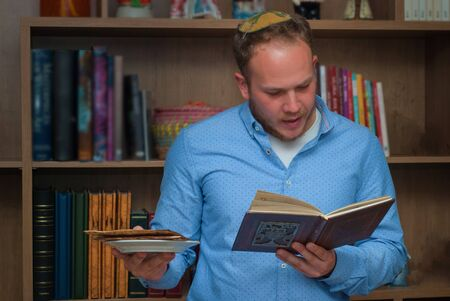 Jewish Family Celebrating Passover.Jewish man reads from the Haggadah as they celebrate Seder. The feast is celebrated on the first night of Passover, holiday commemorating the Jews exodus from Egypt.