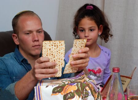Jewish Family Celebrating Passover.Jewish man blessing on Matzah as they celebrate Seder. The feast is celebrated on the first night of Passover, holiday commemorating the Jews exodus from Egypt. 免版税图像