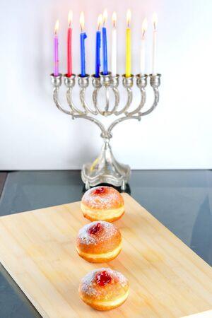 Image of jewish holiday Hanukkah background with menorah traditional candelabra also called a Hanukiyah, jelly or jam doughnut sufganiyot and burning candles. Stock Photo