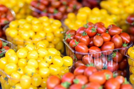 Red and yellow cherry tomato. Harvest. Many little tomatoes. Colorful food textures.