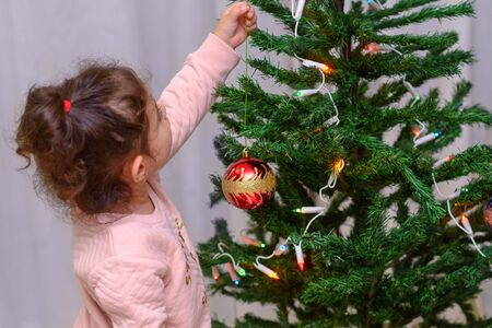 Adorable little girl decorating a Christmas tree with red glass baubles at home.