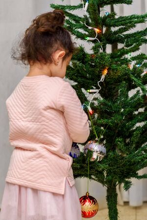 Adorable little girl decorating a Christmas tree with glass baubles at home.