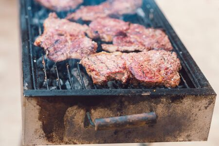 Closeup of delicious beef steaks roasted on barbecue grill. Organic meat roasted on rustic charcoal barbecue.