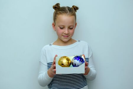 Happy Little Fashion Teen Blonde Girl with freckles holding cardboard boxes with gift and Christmas tree balls. Surprised young teenage girl with trendy hair bun over white grey background.