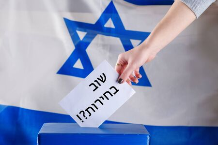 Israeli woman votes on election day. Hebrew text elections again on voting paper over Israel flag background. Israel moves closer to third elections after fails to form government.