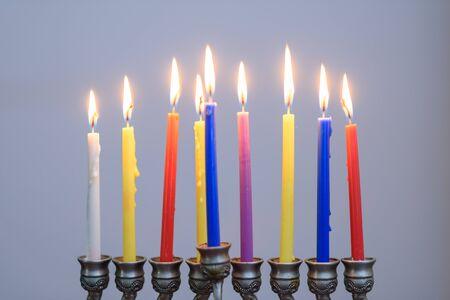 Jüdischer Feiertag Chanukka-Hintergrund mit Menora und bunten Kerzen. Die Menschen feiern Chanukka, indem sie Kerzen auf einer Menora, auch Chanukiya genannt, anzünden.