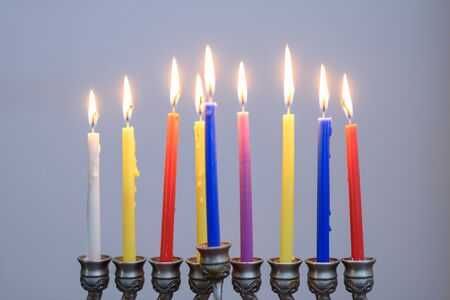 Jewish holiday Hanukkah background with menorah and colorful lighting candles. People celebrate Chanukah by lighting candles on a menorah, also called a Hanukiyah.