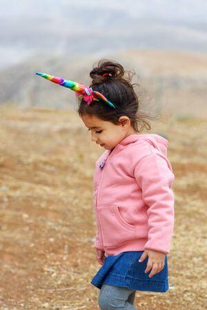 Adorable little preschool girl wearing cute unicorn headband.