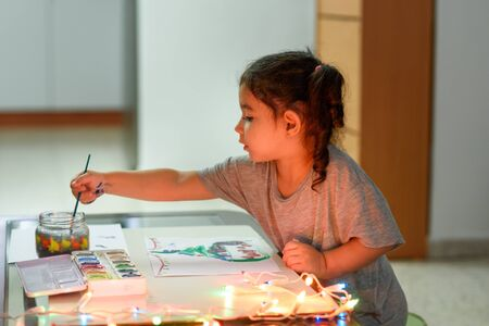 Portrait of cute little girl drawing at home with Christmas decorations. Real life, happy moments, cozy home.