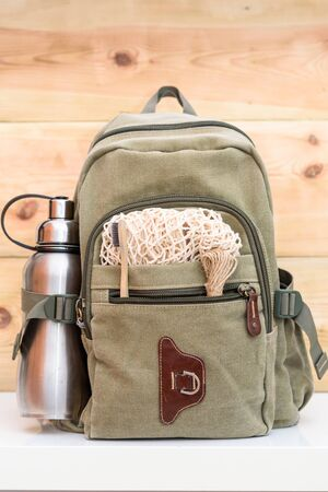 Zero waste travel. Backpack with stainless steel plastic free reusable water bottle, natural reusable cotton mesh grocery bag, eco-friendly bamboo toothbrush, rope natural jute twine hemp linen cord. Stock Photo