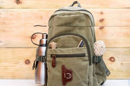 Zero waste travel. Backpack with stainless steel plastic free reusable water bottle, natural reusable cotton mesh grocery bag, eco-friendly bamboo toothbrush, rope natural twine hemp linen cord.