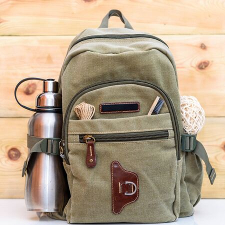 Zero waste travel. Backpack with stainless steel plastic free reusable water bottle, natural reusable cotton mesh grocery bag, eco-friendly bamboo toothbrush, rope natural jute string twine cord. Stock Photo
