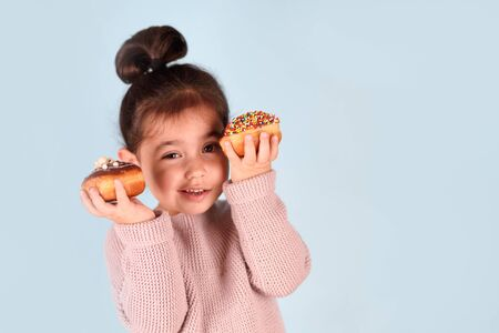 Little happy cute girl eating donuts on blue background. Child having fun with donut looking tricky.