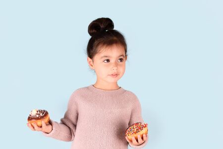 Little happy cute girl holding donuts on blue background.