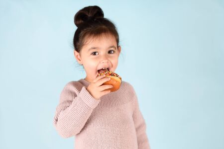 Little happy cute girl eating donut on blue background.
