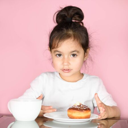 Little happy cute girl eating donut and drinking tea.