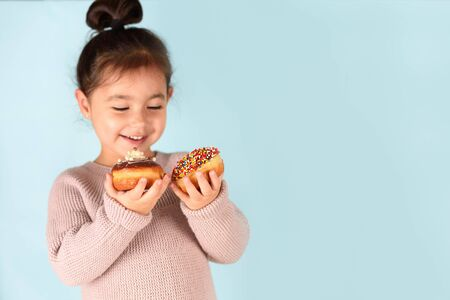 Little happy cute girl eating donuts on blue background. Child having fun with donut. 写真素材