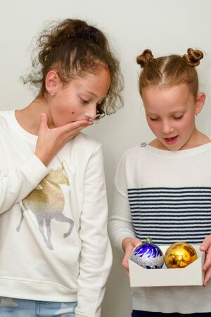Two Surprised young teenage girl with hair bun over white background. Child holding baubles decoration for christmas tree.