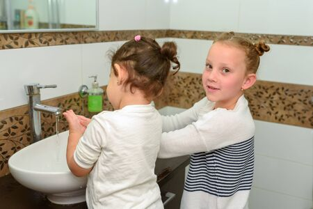 Two little girls in bathroom washing hands. Cute sweet children play in water. Healthy, Childs and Peoples Hygiene concept.