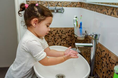 Little toddler girl in bathroom washing hands. Cute sweet baby play in water. Healthy, Childs Hygiene concept.