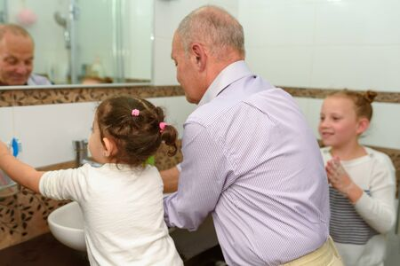 Little happy toddler girls and grandfather in bathroom washing hands. Healthy, Childs and Peoples Hygiene concept. Selective focus on little brunette girl.