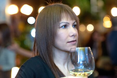 Beautiful woman drinking wine at party on blurred lights festive background.